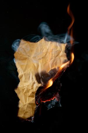 burning piece of crumpled paper on black background Reklamní fotografie