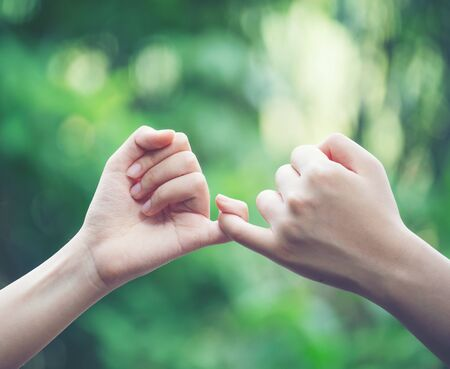 Las manos enganchan el dedo meñique del otro en el fondo de la naturaleza, concepto de promesa