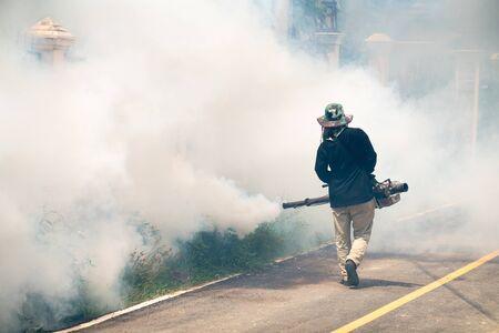El hombre usa la máquina de fumigación de mosquitos para matar al mosquito portador del virus Zika y la fiebre del dengue en la casa