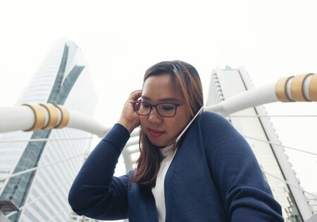 businesswoman walking outdoor and talking on mobile phone