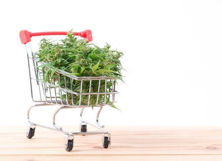 fresh marijuana flower in shopping cart on table