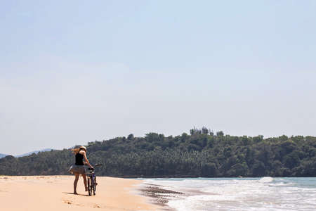 girl with bicycle on a sand shore Stock Photo