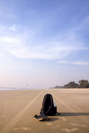 black backpack and pair of shoes on sand beach