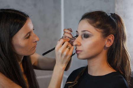 Makeup artist applying eyes makeup