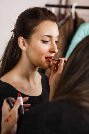 Makeup artist applying lipstick