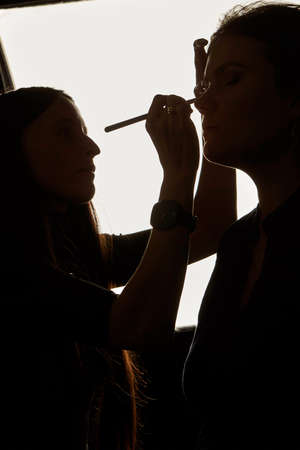 Silhouette photo of makeup artist working