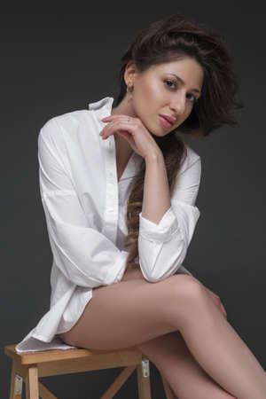 portrait of brunette beautiful girl sitting in white shirt