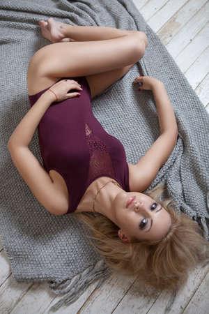 blonde girl in burgundy lingerie lying on the floor