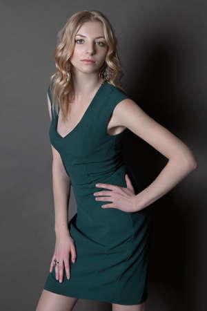 studio portrait of blonde young girl in green dress standing on dark grey background