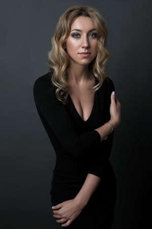 portrait of beautiful woman in black dress standing on dark background Stock Photo