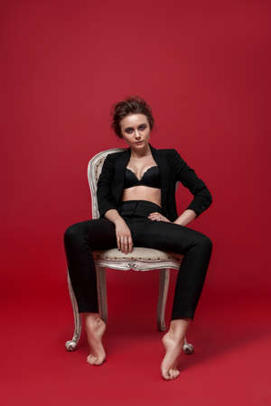 portrait of young girl in black suit on red background sitting pose