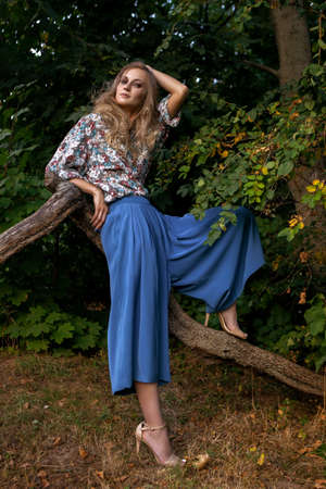 girl in blue clothes leaning on a branch of a tree Stock Photo