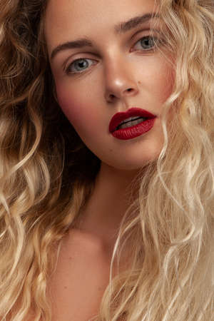 beauty portrait of a female with long wavy blonde hair with makeup Stock Photo