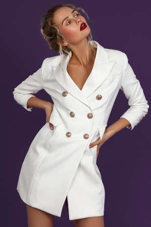fashion portrait of blonde girl standing purple background