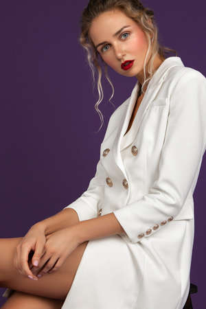 blonde girl with long wavy hair sitting on purple background