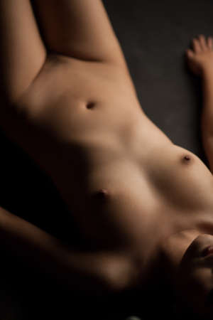 nice breast: naked girl lying down on the black background