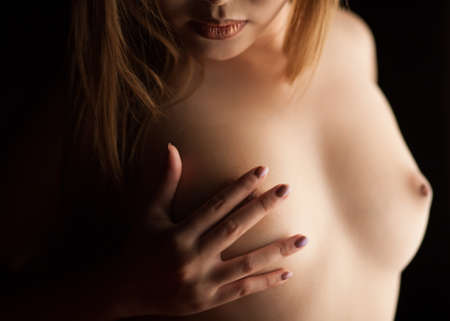 Teen girl naked body. The touch of her soft breast. Stock Photo