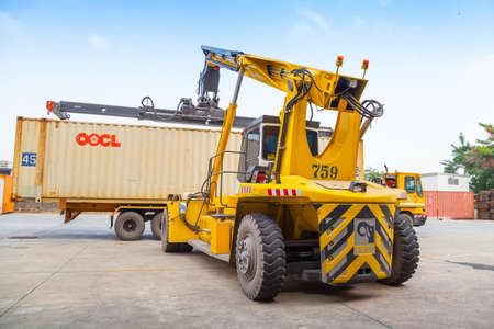 famous industries: Bangkok, Thailand - October 14: Kalmar's reach-stacker loading container in Bangkok Port. October 16, 2014. Kalmar's history goes back over 60 years when it was first formed as the famous lift truck marquee, Coventry Climax, Kalmar Industries purchase