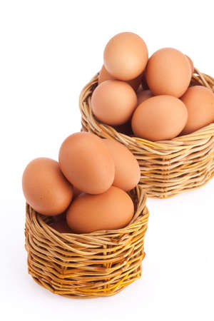 protien: Eggs in 2 wicker baskets on isolated white background. Shallow focus on front basket.