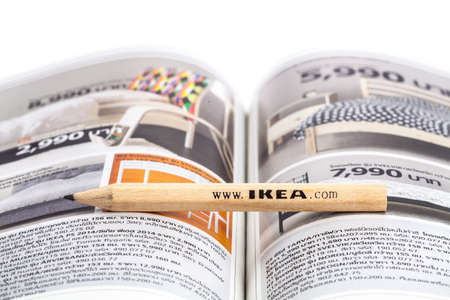 retailer: SONGKHLA THAILAND - JANUARY 27, 2015: IKEA pencil placed between the central ridge of the IKEA catalog walleye edition Thailand . IKEA Founded in Sweden in 1943, Ikea is the worlds largest furniture retailer. Editorial