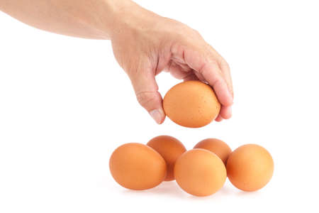 Hand pick up egg from white background photo