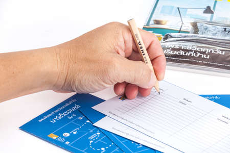man s: SONGKHLA THAILAND - JANUARY 27, 2015: Man s hand holding a pencil to write an IKEA shopping list . IKEA Founded in Sweden in 1943, Ikea is the worlds largest furniture retailer.