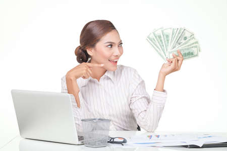 carreer: Asian business woman hold some of bank notes in hand and point with the another hand ,smiling face. isolated on white Stock Photo