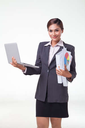 web feed: Business woman using laptop and hold files in another hand, smiling face. Shot in white background
