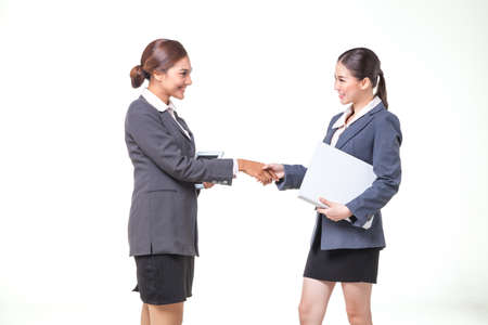 carreer: Two asian business women shake hand together on white background Stock Photo