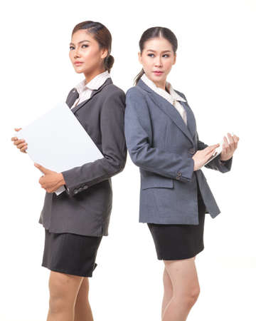 carreer: Two asian business women hold digital tablet. They wear suit and stand on white background Stock Photo