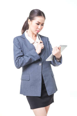 web feed: asian business women working with digital tablet. She is thinking about new project. shot on white background Stock Photo