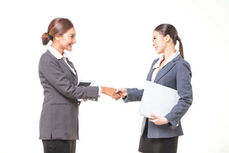asian business women: Two asian business women shake hand together on white background Stock Photo