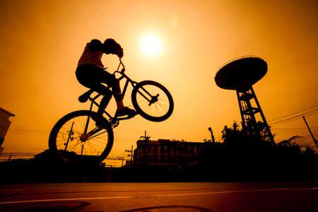bicicleta: Silueta del hombre joven en bicicleta BMX saltar en la ciudad