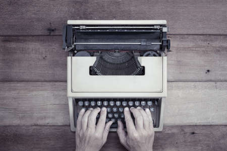 type writer: Human hand on vintage type writer wich place on wooden table. Stock Photo