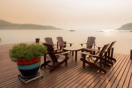 Luxury resort on The Dam of Thailand. Set of Wooden Chair on Terrace beside by The Beautiful lake surrounded by forest and mountain.
