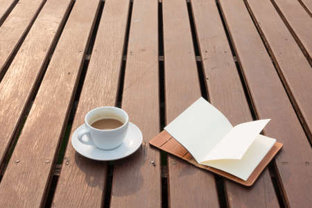 Coffee cup and notebook place on wood terrace Stock Photo