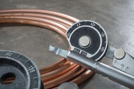 copper pipe: Copper pipe bender tools for installation of air conditioning. Place on vintage concrete floor with copper pipe