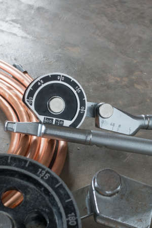 Copper pipe bender tools for installation of air conditioning. Place on vintage concrete floor with copper pipe