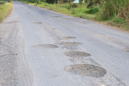 Damage road in south of Thailand. Many holes and cracked on street surface.