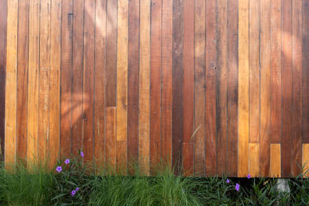 The exterior of wooden wall with grass on bottom. Stock Photo