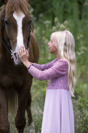 innocent blonde girl with horse in forest. beautiful Caucasian girl with long blonde hair in a pink dress looking at the horse and hugs it. innocent childhood concept. Girl in hipster style 版權商用圖片