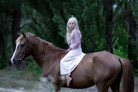 Girl in hipster style on brown horse. beautiful caucasian girl with long blonde hair in a pink dress rides a brown horse in the forest. natural beauty concept. Fashion illustration. nature background