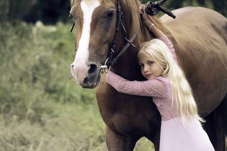 innocent blonde girl with horse in forest. beautiful Caucasian girl with long blonde hair in a pink dress lies on a brown horse and hugs her. innocent childhood concept. barefoot child on horseback.