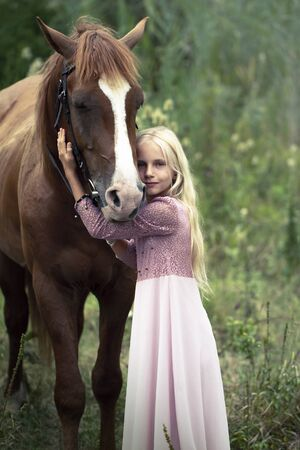 innocent blonde girl with horse in forest. beautiful Caucasian girl with long blonde hair in a pink dress hugs a brown horse. innocent childhood concept. natural beauty. hipster style.