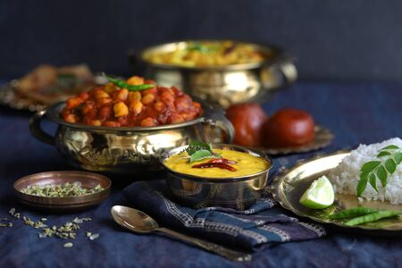 dishes of national Indian cuisine on a dark blue background. traditional Indian home-cooked dinner. rice, dal, sabji, aloo parantha, gulabjamun, masala