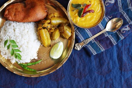 traditional Indian home-cooked dinner. dishes of national Indian cuisine on a dark blue background. rice, dal, sabji, pakora. top view, copy space
