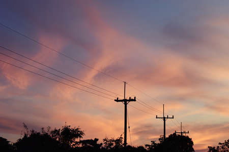 Electricity poles at the roadside with beautiful blue sky before sunset,Photos back - light at the horizon began to turn orange with purple and pink cloud, Dramatic cloudscape area Stock Photo