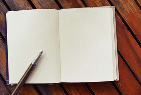 Pen and book open blank pages on old brown wood paneling, Space on the page for images or text