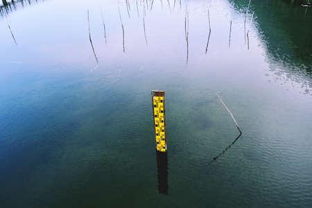 Water level gauge or Staff Gauge on blue water in the wetland