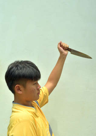 Asian teenage men holding a kitchen knife sharp and pointed on green background, Acne-prone face of adolescent male, Halloween horror concept